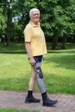 Glücklicher älterer Mann, der mit dem prothetischen Bein geht Lizenzfreie Stockfotografie