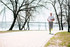 Glücklicher älterer Mann, der in Park läuft lizenzfreies stockfoto