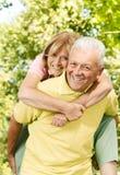 Glücklicher älterer Mann, der piggyback gibt stockbilder