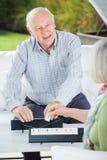 Glücklicher älterer Mann, der Rummy With Woman spielt Stockfotografie
