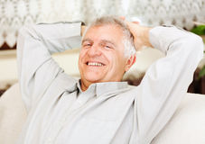Glücklicher älterer Mann, der sich zu Hause entspannt Stockfotografie