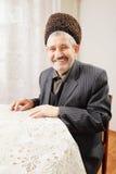 Glücklicher älterer Mann, der am Tisch sitzt stockbild