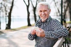 Glücklicher älterer Mann, der Titelliste vorwählt stockfotos