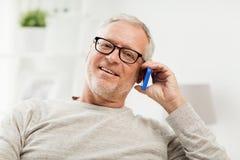 Glücklicher älterer Mann, der zu Hause um Smartphone ersucht Stockfoto