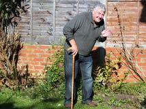 Glücklicher älterer Mann mit dem Wellenartig bewegen des gehenden Steuerknüppels. Stockfotos