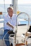 Glücklicher älterer Mann am Rad eines Segel-Bootes Lizenzfreie Stockfotos