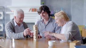 Glücklicher älterer Mann und Frau, die Brettspiel mit seinem Enkel spielt stock video
