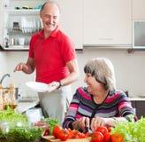 Glücklicher älterer Mann und reife Frau, die Aufgaben tut Stockbild
