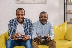 glücklicher älterer Vater und erwachsener Sohn unter Verwendung der Steuerknüppel und des Lächelns lizenzfreies stockfoto