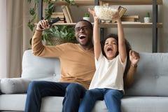 Glücklicher überglücklicher schwarzer Vater mit der Kindertochter, die Fernsehspiel aufpasst lizenzfreies stockfoto