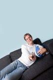 Glücklicher überwachender Sport des jungen Mannes auf Fernsehapparat Stockfoto