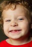 Glücklicher 2 Jahr-alter blonder Junge, der einen Zahn verfehlt Stockfotografie
