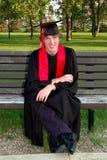 Glücklicher Absolvent in der Schutzkappe und im Kleid Stockfoto