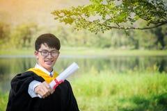 Glücklicher Absolvent Glücklicher asiatischer Mann in der Staffelung bekleidet holdin auf Na Stockbild