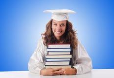 Glücklicher Absolvent mit vielen Büchern auf Weiß stockfotografie