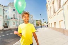 Glücklicher afrikanischer Junge im gelben T-Shirt mit Ballon Stockbild