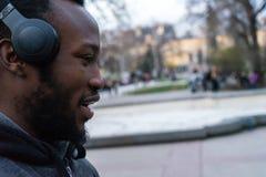 Glücklicher afrikanischer junger Kerl mit einem Bart und Kopfhörer in einem Park lizenzfreies stockbild