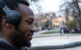 Glücklicher afrikanischer junger Kerl mit einem Bart und Kopfhörer in einem Park stockbilder