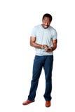 Glücklicher afrikanischer Mann, der Smartphone verwendet Stockfotos