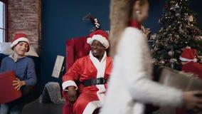 Glücklicher afrikanischer Mann in rotem Weihnachtsmann-Kostüm, das im Stuhl während lächelnde Kinder springen um ihn sitzt stock footage