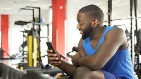 Glücklicher afro-amerikanischer Mann, der an der Turnhalle und am aufpassenden Video auf Mobiltelefon sitzt stock video