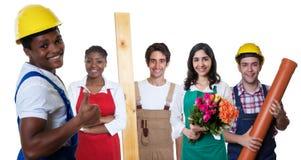 Glücklicher Afroamerikanerbauarbeiter mit Gruppe anderer Arbeitskräfte lizenzfreies stockbild