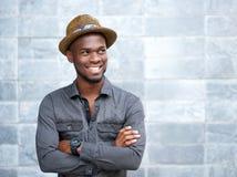 Glücklicher Afroamerikanerkerl, der mit den Armen gekreuzt lächelt Stockfotos