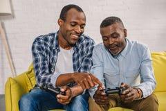 glücklicher Afroamerikanervater und erwachsener Sohn unter Verwendung der Steuerknüppel zusammen stockfotos