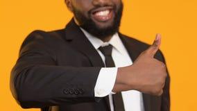 Glücklicher afroer-amerikanisch Mann in der Klage, die sich Daumen, Bankdienstleistungszustimmung zeigt stock footage