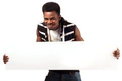 Glücklicher Afromann, der leeres Anschlagbrett hält Lizenzfreie Stockfotos