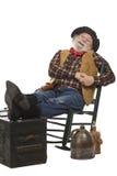 Glücklicher alter Cowboy in Schwingstuhl mit Füßen oben Stockfoto