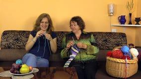 Glücklicher alter Großmutter Knit mit Krankenschwestermädchen auf Sofa im Pflegeheim stock footage