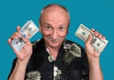 Glücklicher alter Mann, der Dollarscheine hält Stockfotos