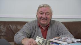 Glücklicher alter Mann, der am Holztisch mit Dollar in seinen Händen nah oben sitzt Positiver Reicher demonstriert sein Geld stock video footage