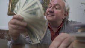 Glücklicher alter Mann, der sein Gesicht mit den Dollar nah oben auflockert Positiver Reicher demonstriert sein Geld lustiger Gro stock video