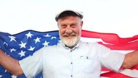 Gl?cklicher amerikanischer Pension?r h?lt US-Staatsflagge Unabh?ngigkeitstag Juli 4 stock video footage
