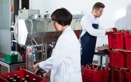 Glücklicher Angestellter, der Maschine verwendet, um Wein abzufüllen Lizenzfreie Stockfotos