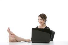 Glücklicher Angestellter, der mit ihren Füßen auf dem Schreibtisch sitzt Stockbilder