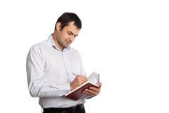 Glücklicher Angestellter schreibt Anmerkungen in Notizbuch Lizenzfreie Stockfotos