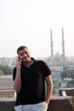 Glücklicher arabischer ägyptischer junger Geschäftsmann, der mit Telefon spricht stockbild