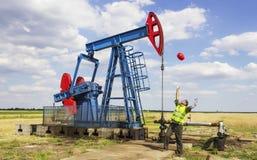 Glücklicher Arbeitskraftwurf sein Sturzhelm vor Ölpumpe Stockbild