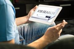 Glücklicher Arbeitssuchende, der versucht, Arbeit unter Verwendung der on-line-Suchmaschine zu finden lizenzfreie stockfotografie