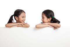 Glücklicher Asiat paart Mädchen hinter weißer leerer Fahne stockbild