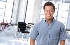 Glücklicher asiatischer Büroangestellter am modischen Arbeitsplatz Stockbilder