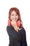 Glücklicher asiatischer Büromädchenaufzug ein roter Dummkopf Stockbild