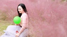 Glücklicher asiatischer Chinesinmädchengefühl-Freiheitstraum, Blumenfeld-Fallparkgrasrasen-Hoffnungsnatur zu beten las Buchballon stockfotos