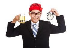 Glücklicher asiatischer Geschäftsmann mit Bier und Uhr um Mitternacht Lizenzfreie Stockfotos