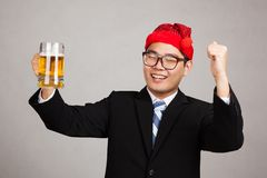Glücklicher asiatischer Geschäftsmann mit Parteihut und -bier Stockbild