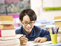 Glücklicher asiatischer Grundschüler, der im Klassenzimmer studiert Stockfotografie
