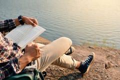 Glücklicher asiatischer Hippie-Mann, der ein Buch im Naturhintergrund liest Stockfotos